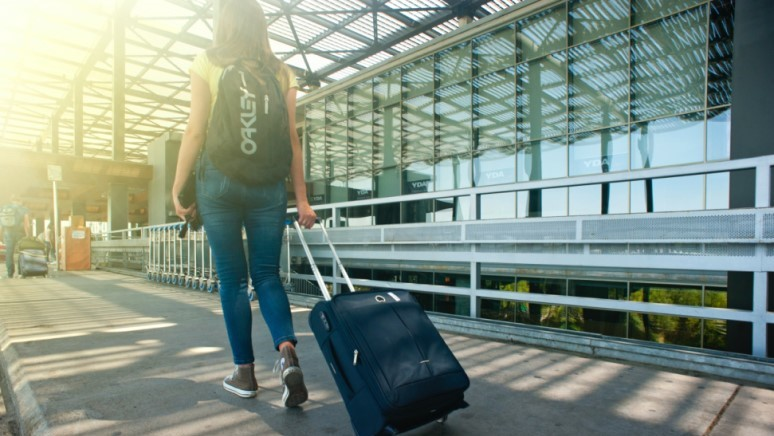 xTEN's Client Youtravel, woman walking on a pathway while strolling luggage
